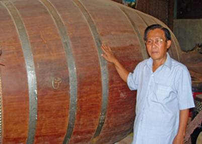 Nghệ nhân Năm Mến bên chiếc trống chầu kỷ lục cao 2,5m, đường kính mặt trống 1,47m – Ảnh: nguồn sgtt.vn (2-2-2008)