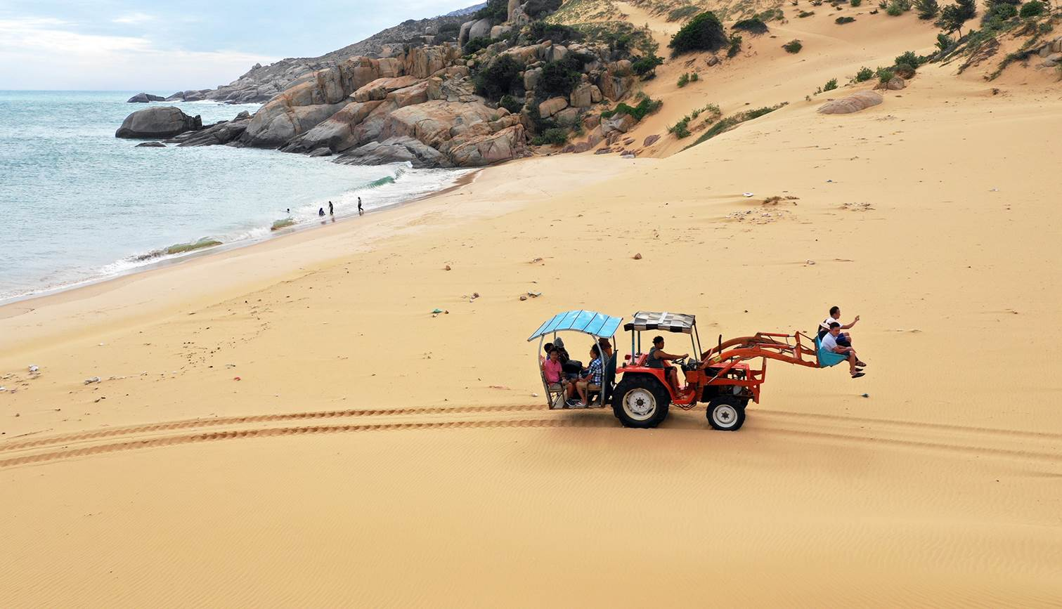 Xe xúc chở khách vượt đồi cát